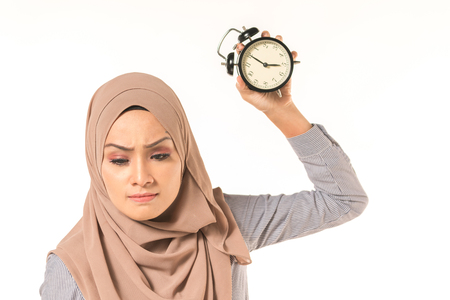 A pretty student holding clock. Time management concept. 免版税图像