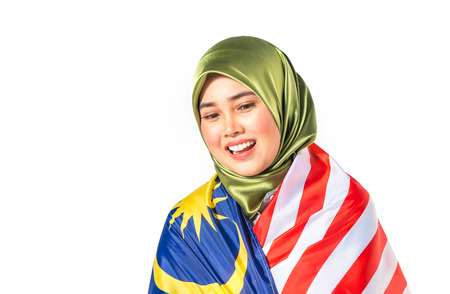 Hijab teenager holding malaysia flag for independence day celebration.