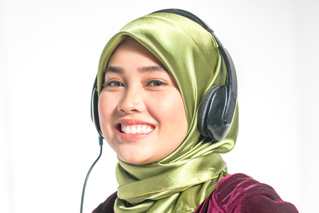 traditional culture: Veiled teenager and headset with entertaiment concept. Stock Photo