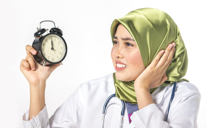 Veiled medical staff with clock. Time management concept. Stock Photo