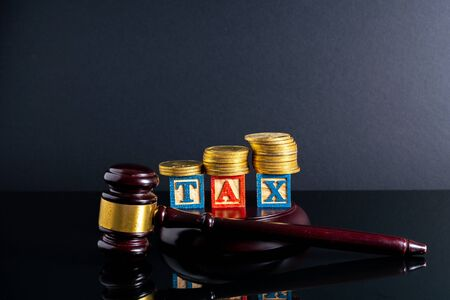 Gavel hammer and stacking coins and tax letter cube with low light view.