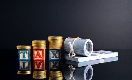 Coins stacking and tax letter cube with low light view.