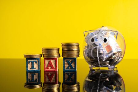 TAX letter and stacking coins with financial concept. Image in low light view.