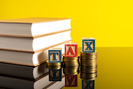 TAX letter and stacking coins with financial concept. Image in low light view. 스톡 콘텐츠