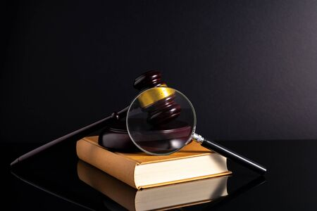 Gavel hammer and book with low light view. Educational concept.