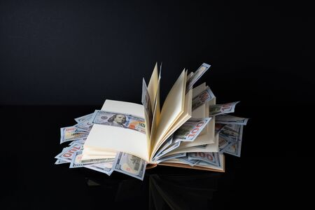 Banknotes and book with white background with financial concept.