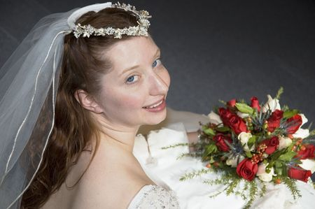 over shoulders: Bride looking back over shoulders with flowers in lap Stock Photo