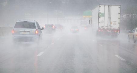 zichtbaarheid: Voertuigen op natte weg in de regen Stockfoto
