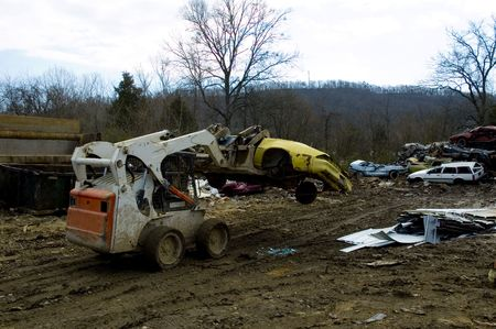 salvage yard: Car being carried to scrap metal pile Stock Photo