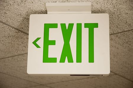 ceiling mounted exit sign with green print