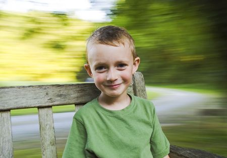 Young boy spinning on a bench.  Blurred background with lots of copy space. 스톡 콘텐츠