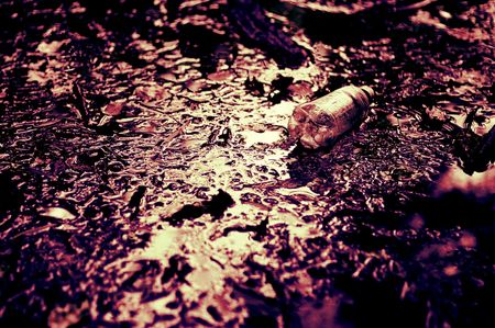 trashed: High contrast concept image showing waterway with trashed plastic bottle