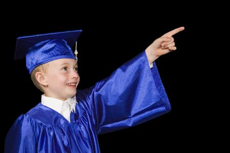 young boy in graduation cap and gown pointing out of frame and smiling