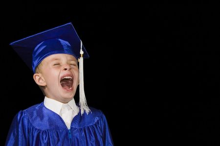 yawning boy on black background dressed in blue graduation cap and gown
