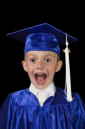 young boy in blue cap and gown with excited surprised look on his face on black background