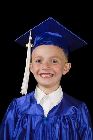 Young smiling boy in blue graduation cap and gown on black background