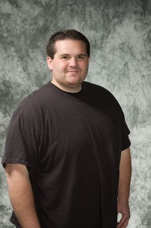 overweight people: overweight young man posing in front of portrait backdrop