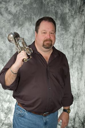 rotund: young man posing with trumpet in front of portrait backdrop Stock Photo