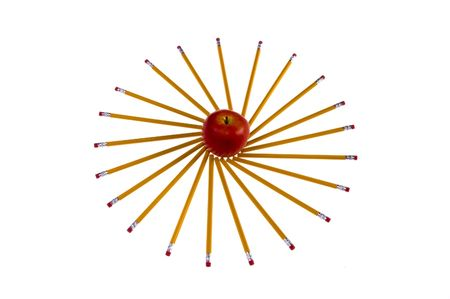 mornings: Red apple with pencils surrounding in sunshine shape perfect for summer mornings, teachers and scrapbooking. Stock Photo