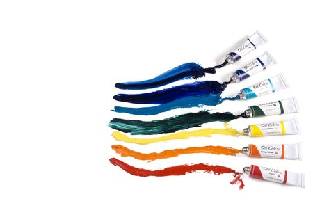Collection of oil paint tubes with paint spread across paper in rainbow colors.