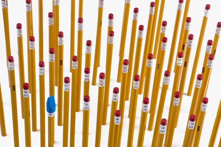 A group of yellow #2 pencils with one blue eraser that is different. Imagens