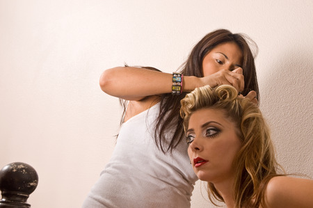 refreshes: Makeup artists refreshes model during shoot Stock Photo