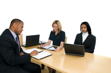 Two women and a man sit at conference table at a business meeting