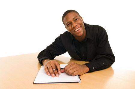 Smiling young black man sitting at table with notebook