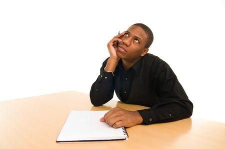 young black man sits daydreaming at table