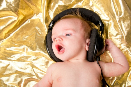 Baby boy on gold background sings along with music from headphones photo