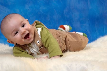 Happy child on the white carpet and the blue mosaic background
