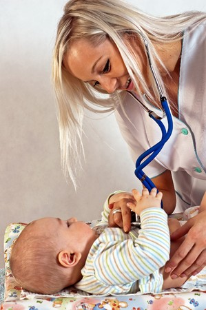 neonate: Young female doctor listening to a babys heart.