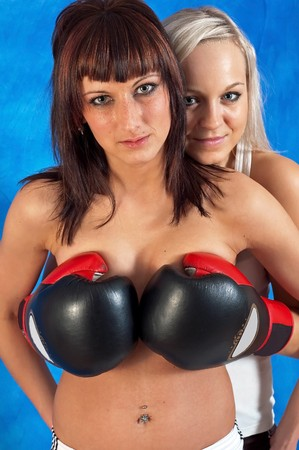 Young sexy girls in boxing gloves on the blue mosaic background