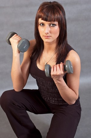 Young woman lifting weights on grey background