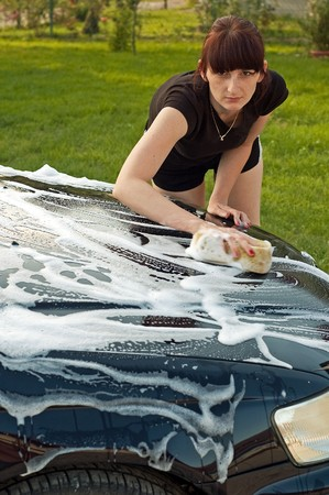 Adult cleaning her car outside