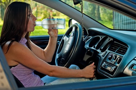 drink and drive: Woman drinking alcohol during a drive in a car