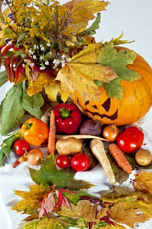 autumn composition of vegetables of leaves and the pumpkin halloween on the white background photo