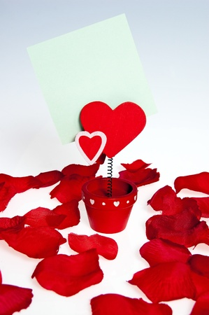 rhyme: Heart-shaped flower with a note attached to the rhyme standing amidst rose petals