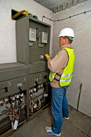 switchgear: Electrician in studying the current-voltage switchgear and state electrical