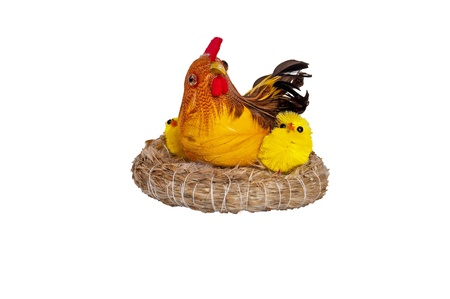 Artificial hen sitting with little chicks in a nest on a white background