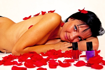 Rose petals and a naked woman on a white background