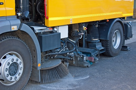 Street sweeper cleans street with brushes and water Stock Photo