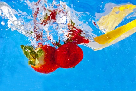 Fresh fruits falling into the water on a blue mosaic background photo