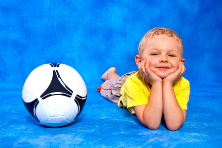 Boy and the ball lying on a blue mosaic background photo