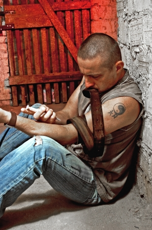 Drug addict injecting himself in the gloomy basement Stock Photo