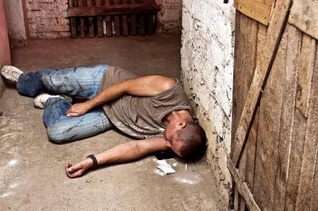 drogadicto: Sobredosis adicto contra el s�tano Foto de archivo
