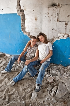 wino: Homeless young couple sitting in the ruins of an old house