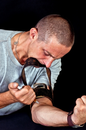 substance abuse: Drug addict injecting himself in the gloomy basement Stock Photo