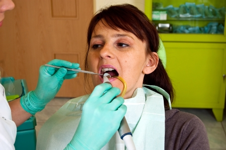 surgery expenses: Dental treatment in a young woman in a dentists office Stock Photo