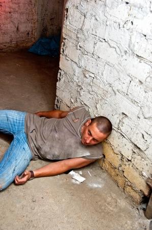 Overdose addict against the basement